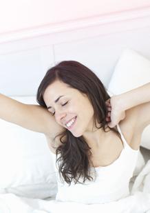 Imagem de uma jovem mulher que acaba de acordar. A imagem ilustra que se pode dormir com um tampão e acordar a sentir-se revitalizada.