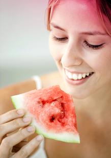 Imagem de uma jovem a comer uma fatia de melancia. A imagem ilustra uma das sugestões para aliviar as dores menstruais: comer fruta ou vegetais com elevado teor de água.