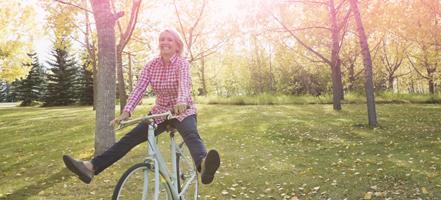 Imagem de uma mulher de bicicleta. A imagem ilustra uma mulher cheia de vida e saudável, como habitualmente, mesmo durante a menstruação.